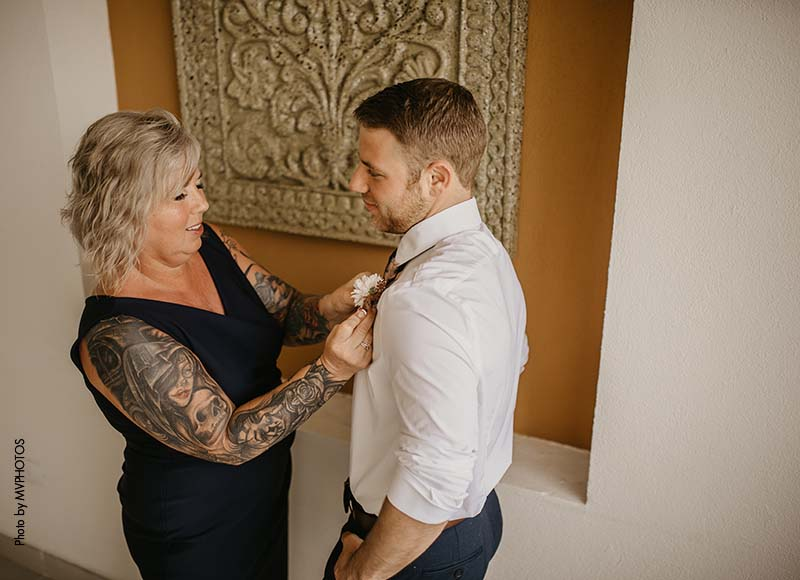 Mother of groom helps put boutonniere on
