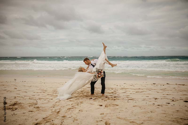 Groom dips his bride on the beach