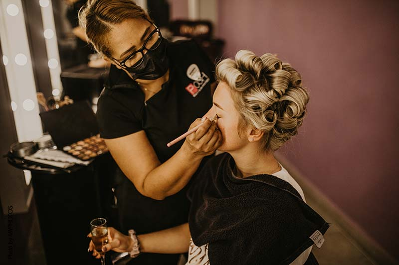 Bride gets makeup and hair done before beachside wedding