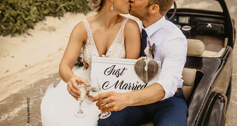 """Couple holds """"Just Married"""" sign as they cheers with champagne"""