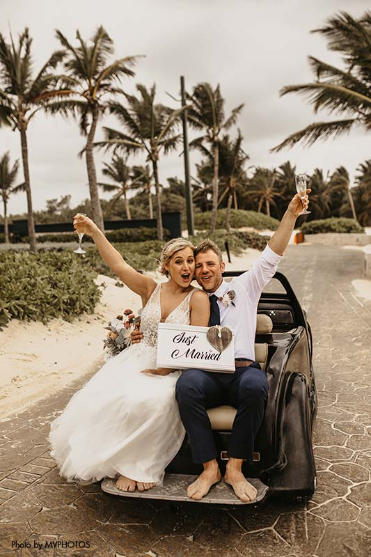 Couple drives away in old school car after beachside wedding