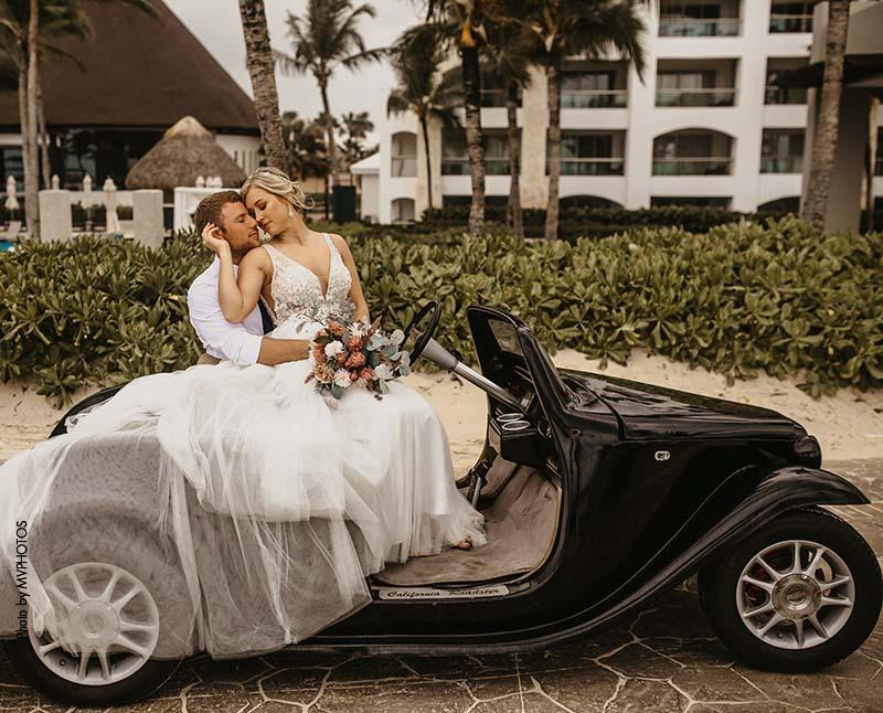 Bride and groom sit on a black vintage car