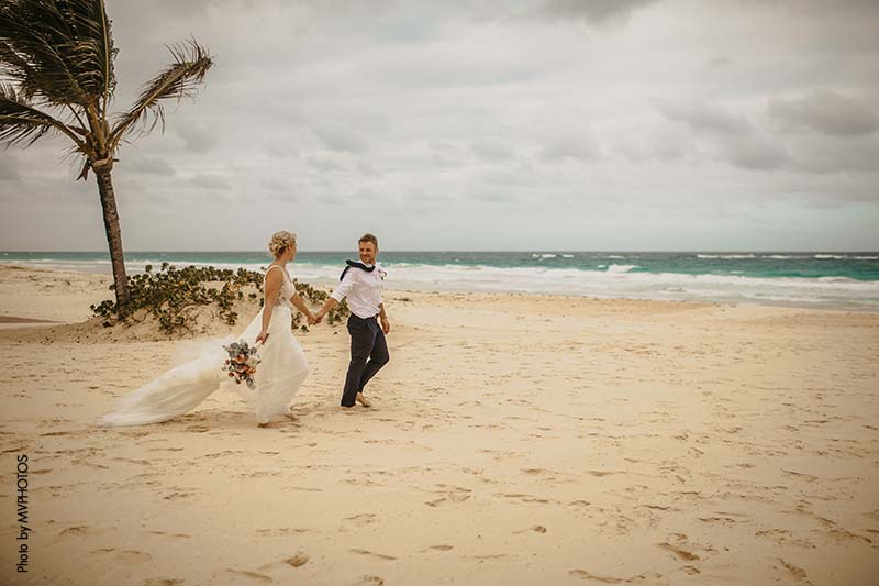 New bride and groom walk along beach