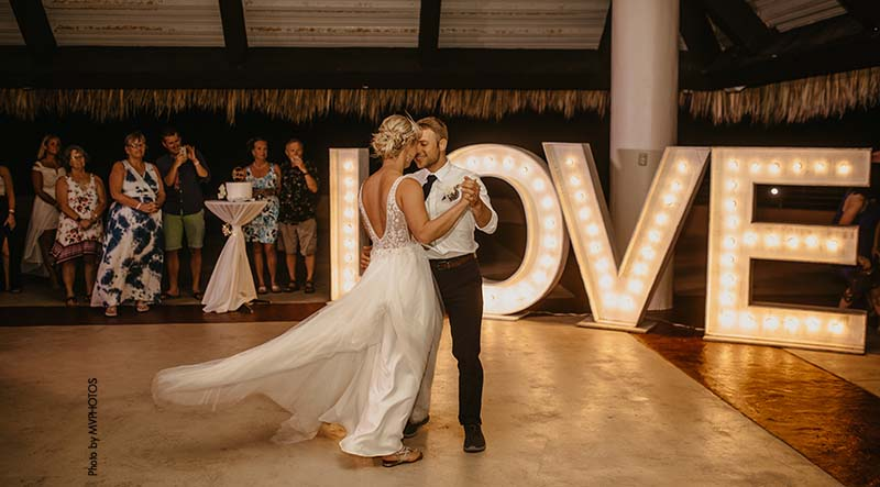 Bride and groom share first dance during beach wedding reception