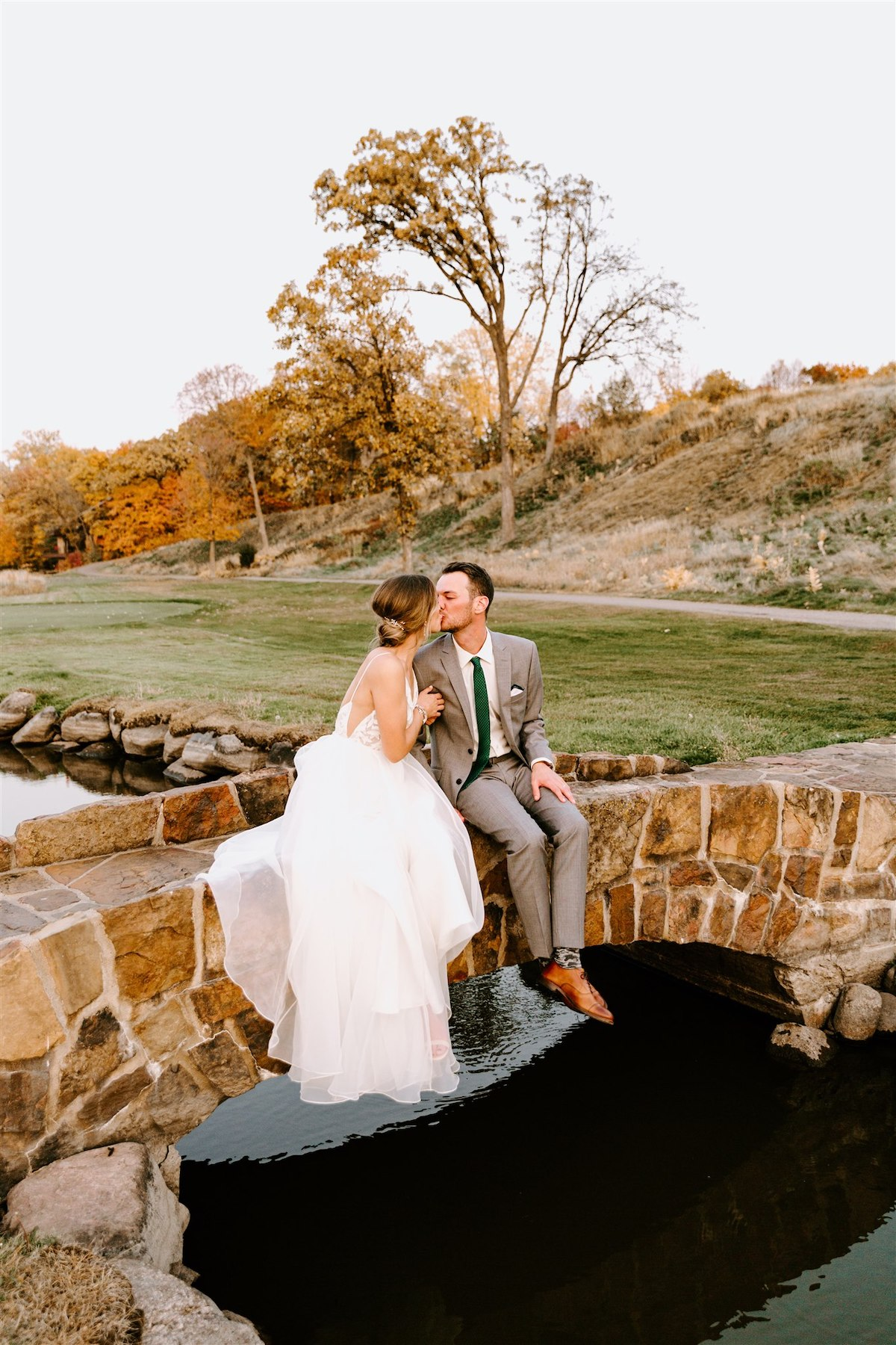 Bride and groom sit on bridge at golf course wedding at Hazeltine National Golf Club in Minnesota
