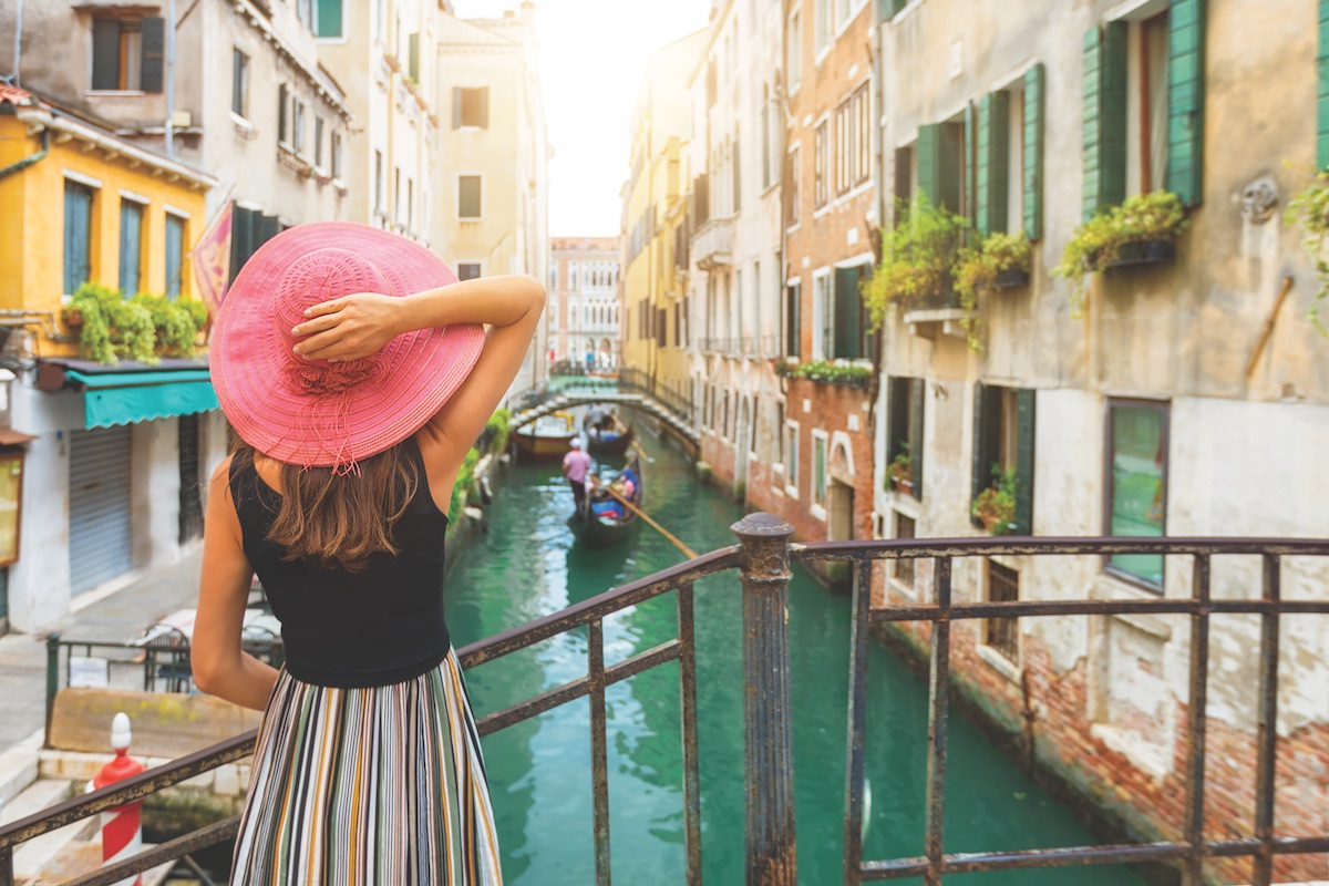 Girl in pink hat overlooks canal