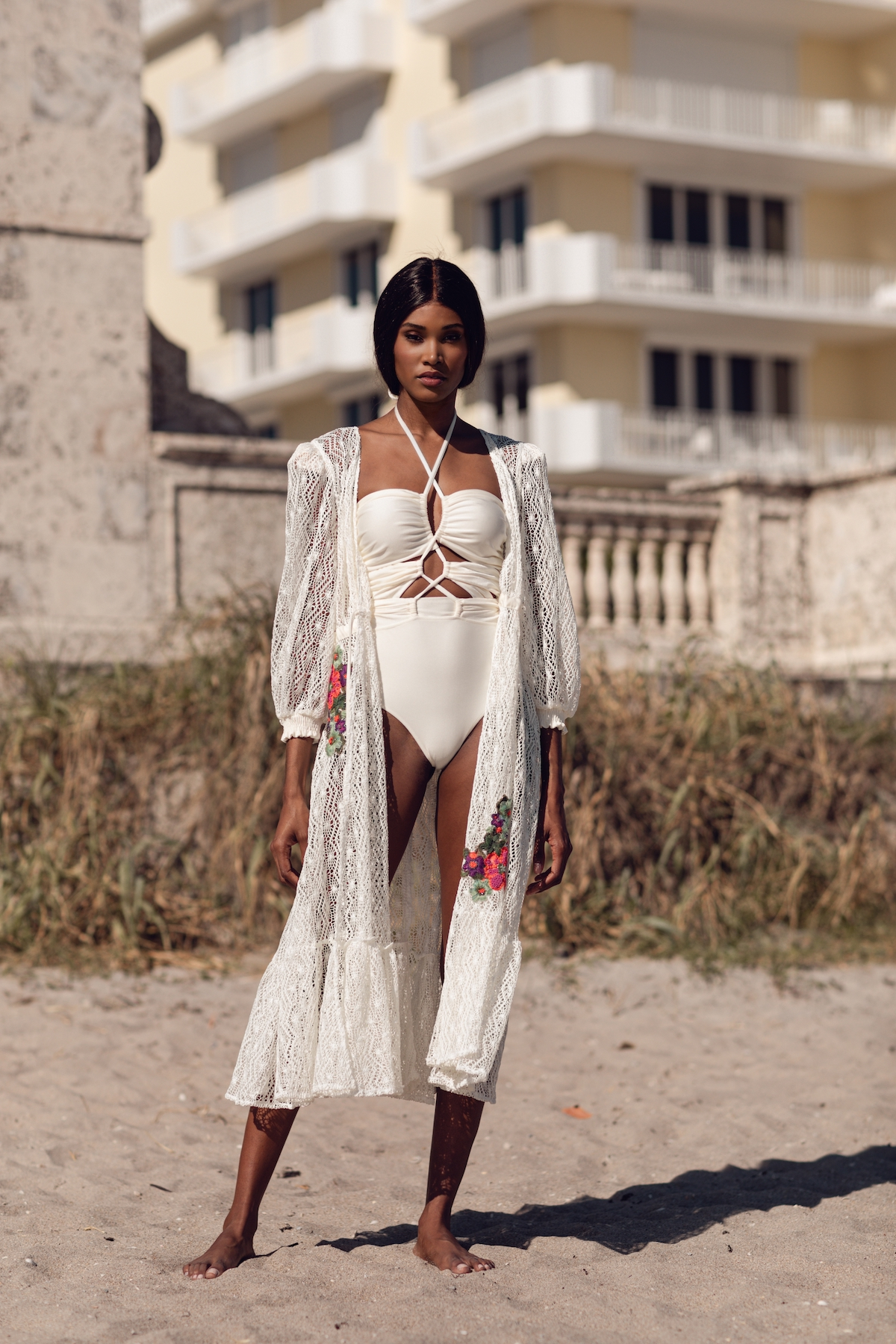 Bridal model poses in white swimsuit and cover up