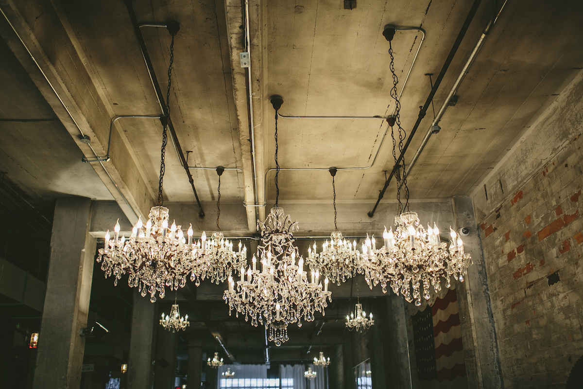 Large glamorous chandeliers hang from ceiling at industrial wedding venue