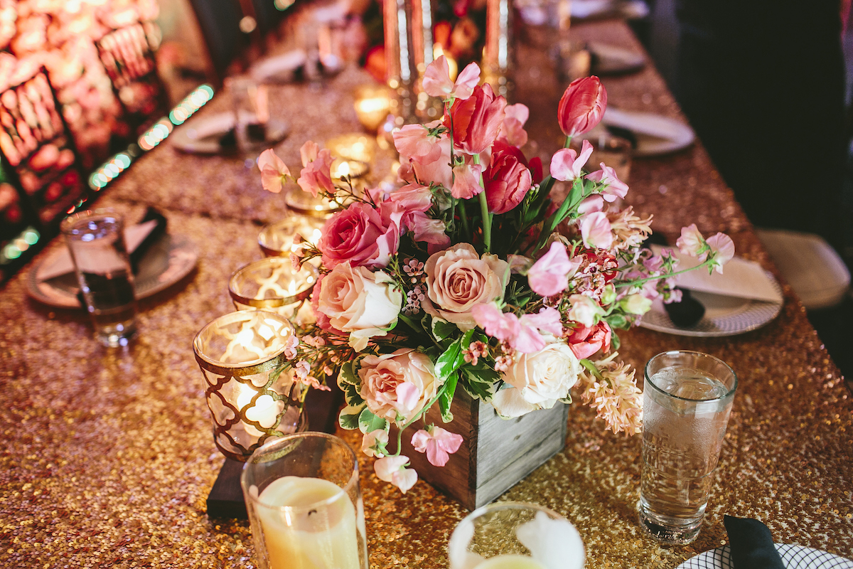 Pink, red, and white roses on table at wedding