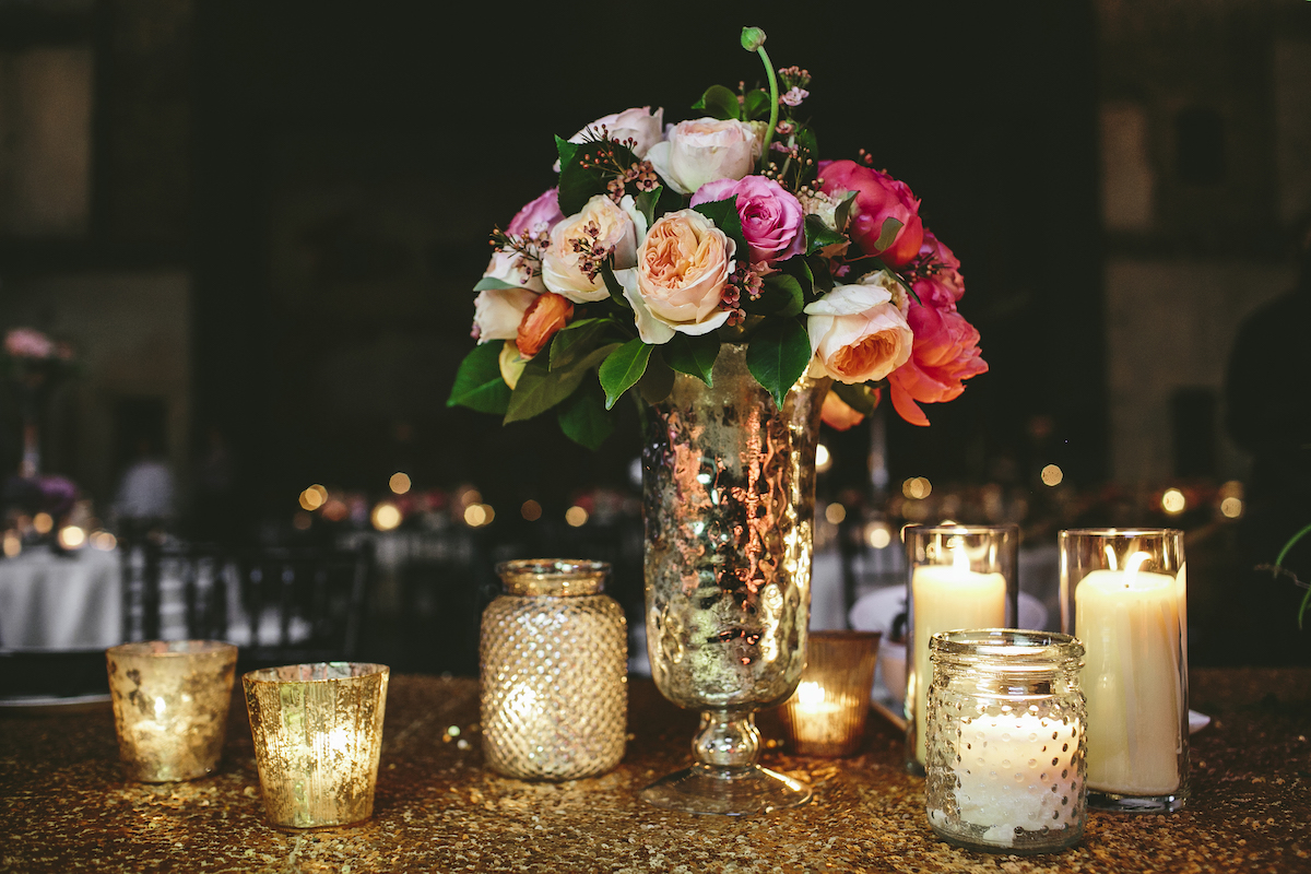 Pink, white, and peach rose bouquet on wedding table in mercury vase