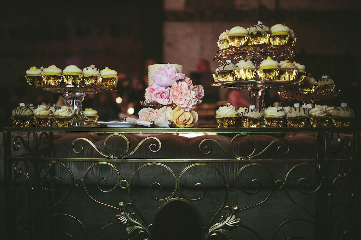 Dessert bar at wedding with cupcakes and a 2-tier floral cake