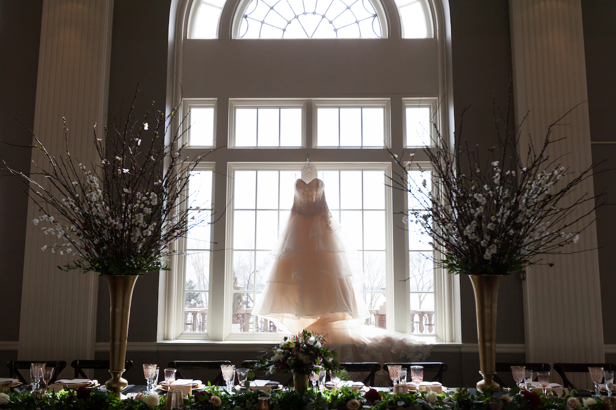Bridal dress hangs from tall window
