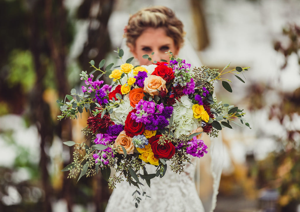 Bright bouquet with colored roses, purples, peaches, red and greenery