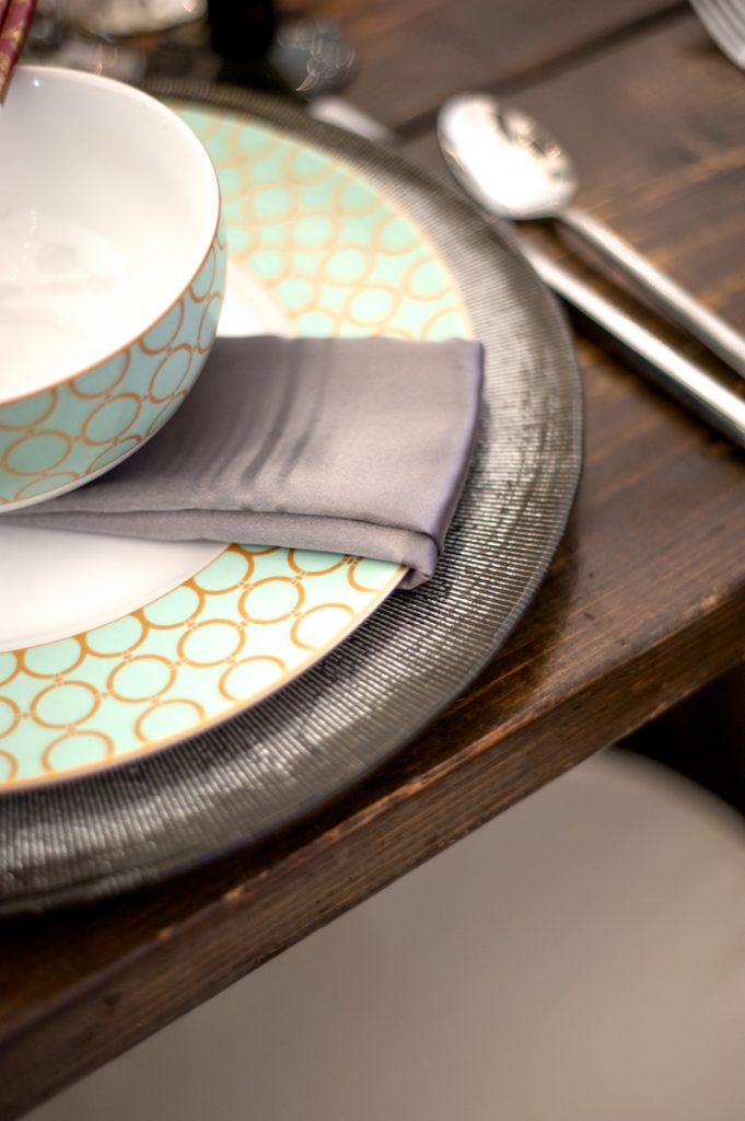 Teal and gold patterned plate sits on top of a silver charger