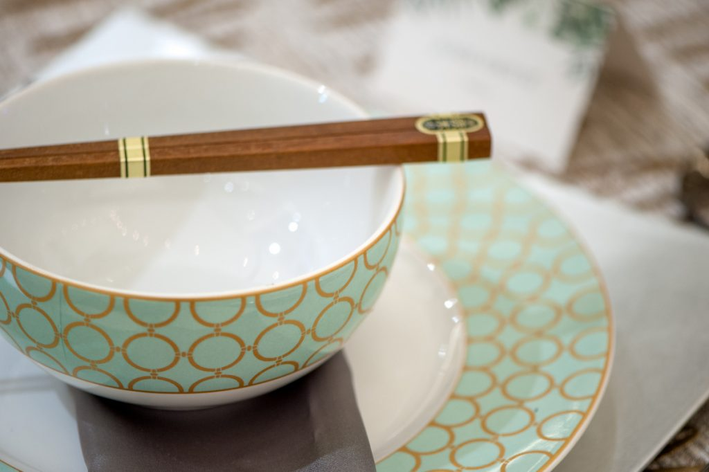 Teal and gold patterned plate and bowl sit on top of a silver charger