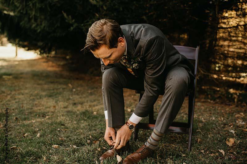 Groom ties shoes in charcoal suit