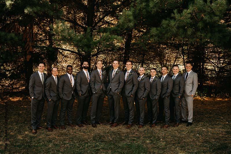 Groomsmen in dark gray suits and floral ties