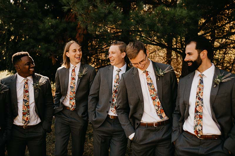 Groomsmen in gray suits laughing