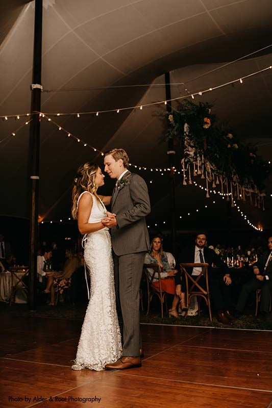 Bride and groom share first dance on dance floor under tent