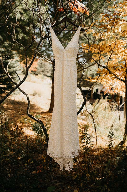 Sleek and detailed bridal gown hangs from tree