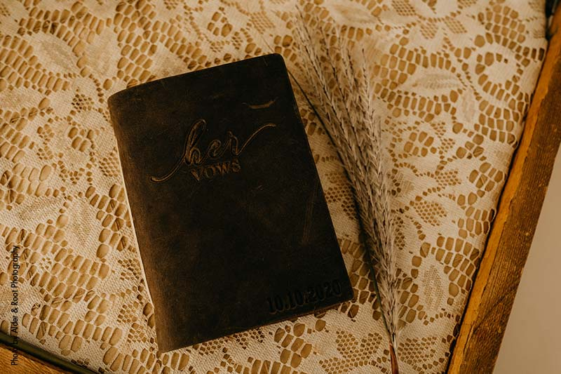 """Dark brown book that says """"Her Vows"""""""