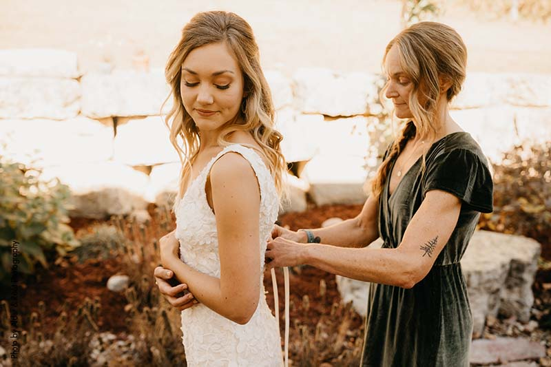Mother of the bride ties bow on bridal gown