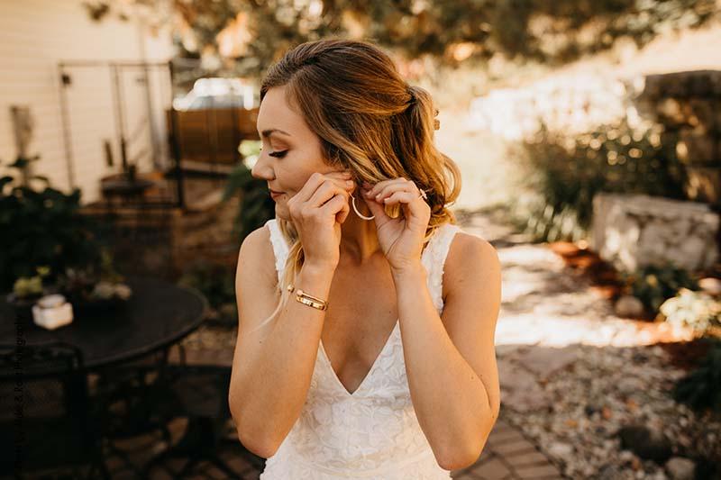Bride puts on her gold hoop earrings