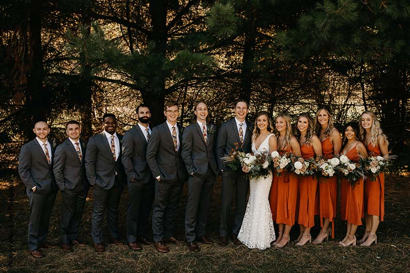 Bridesmaids in orange midi dresses and groomsmen in gray suits