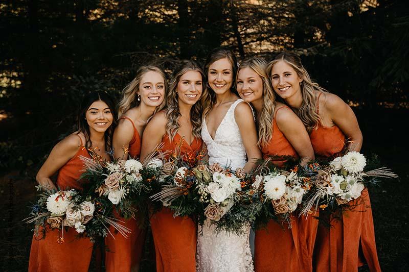 Bridesmaids in burnt orange dresses pose with bride