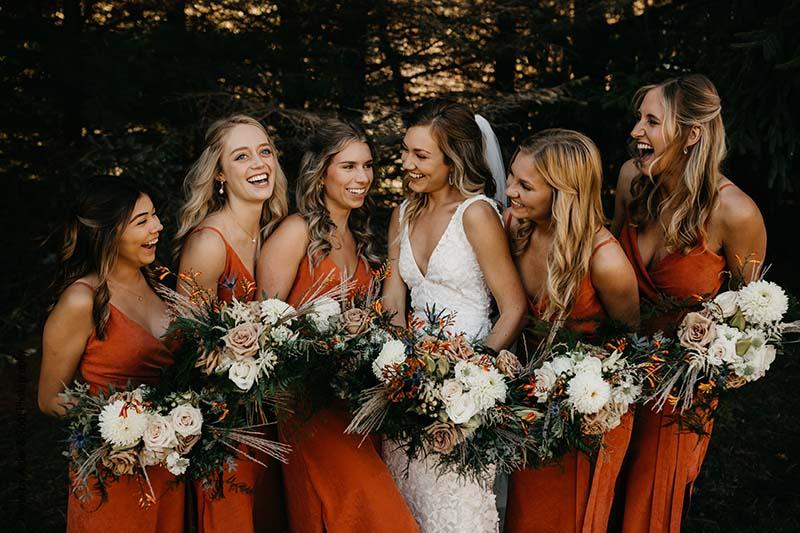 Bridesmaids in burnt orange dresses laugh with bride