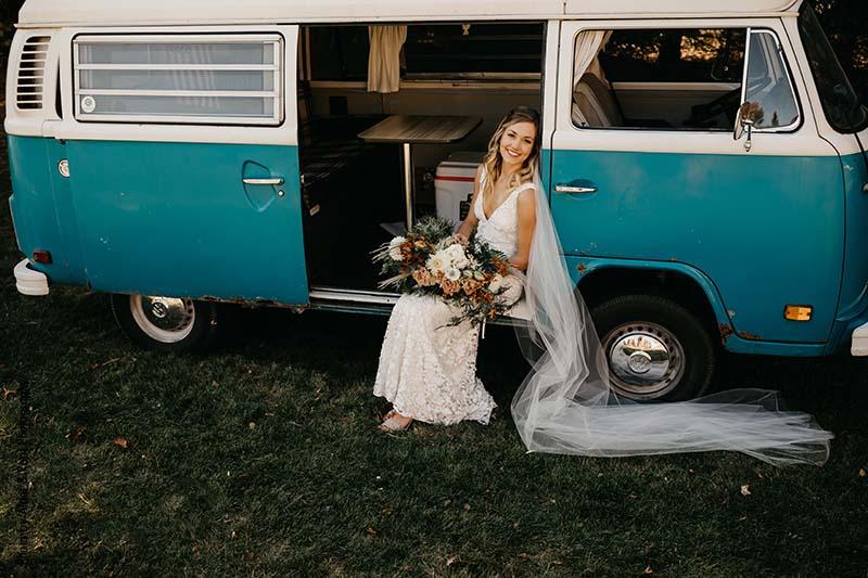 Bride sits in blue Volkswagen van