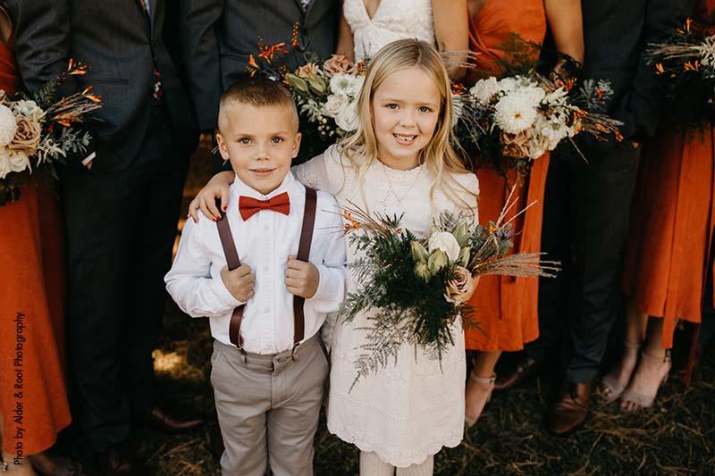 Ring bearer in gray pants and orange tie, flower girl in off-white dress