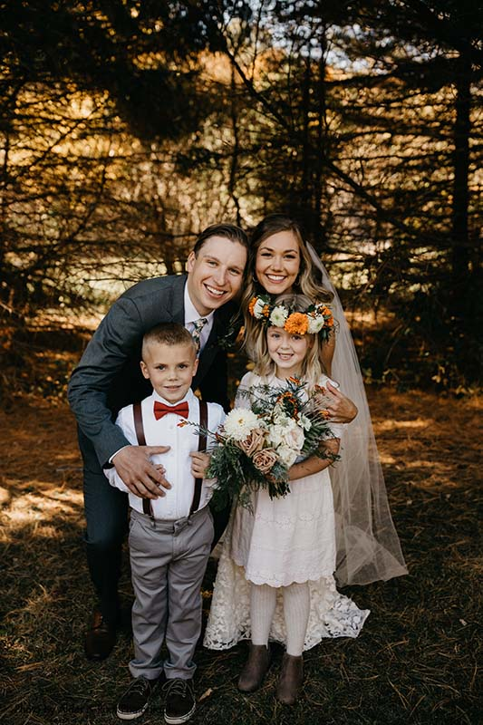 Bride and groom pose with ring bearer and flower girl at outdoor wedding