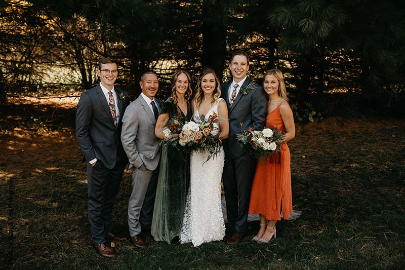 Bride and groom poses with family members