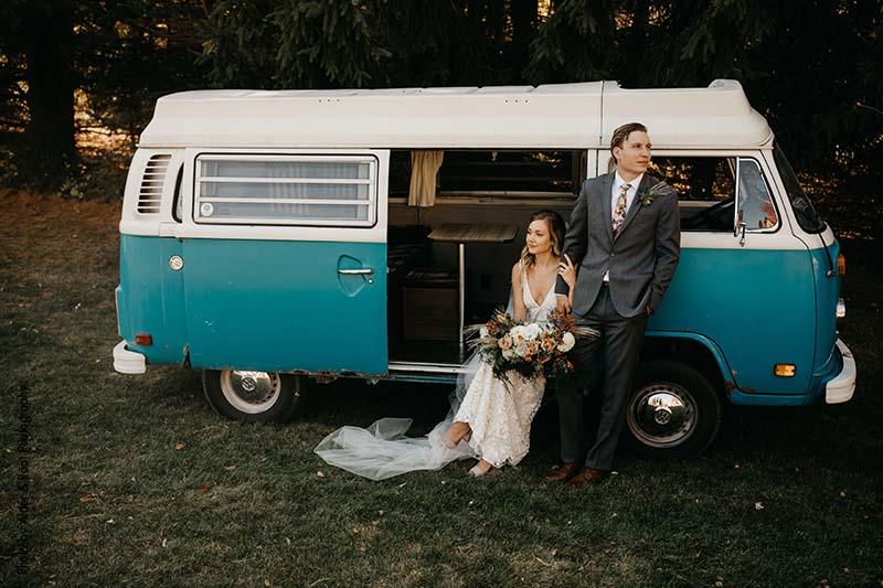 Bride and groom pose with blue vintage Volkswagen van