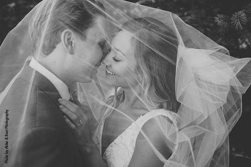 Bride and groom hide under veil