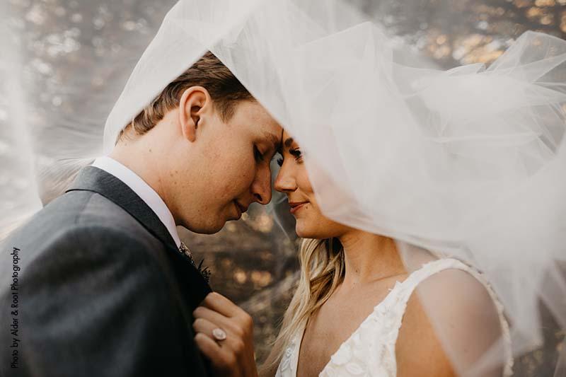 Bride and groom pose under bridal veil