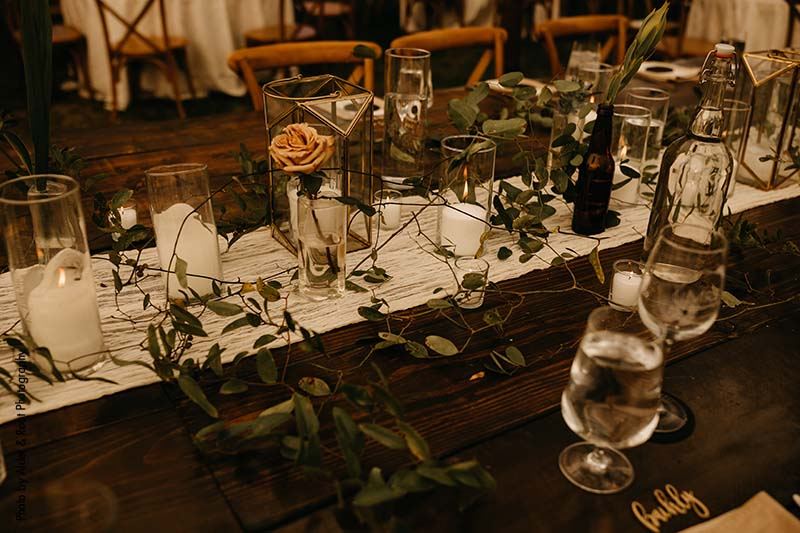 Head table wedding design with greenery and wood elements