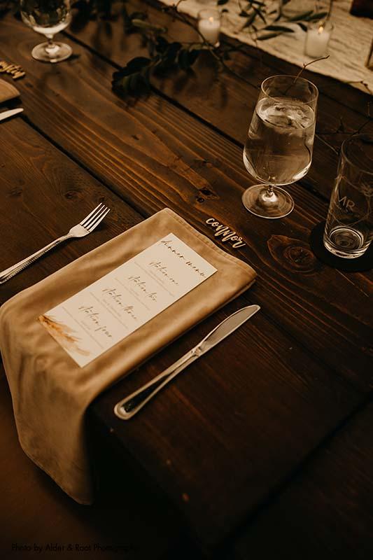 Beige napkin with simple white and orange wedding dinner menu