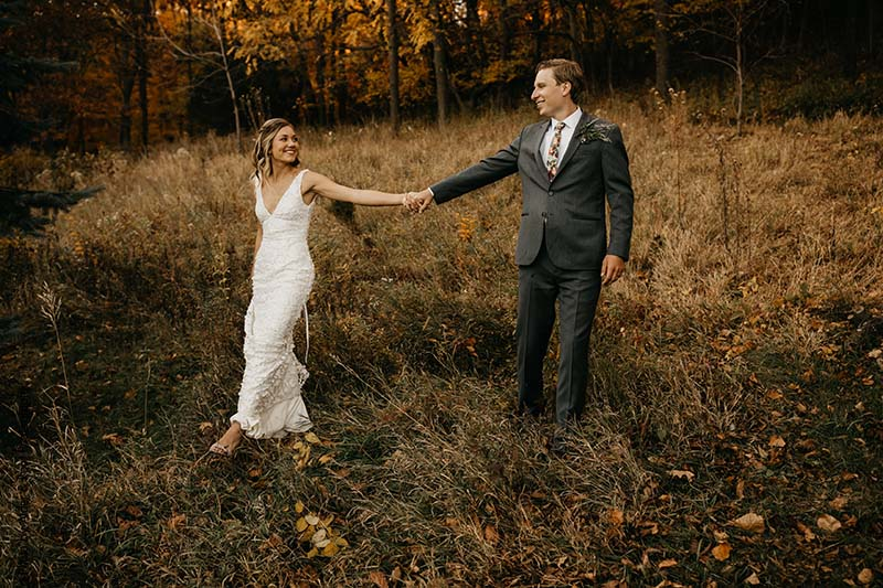 Bride and groom walk through fields at outdoor wedding in MN