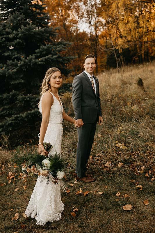 Bride and groom walk through fields after outdoor wedding
