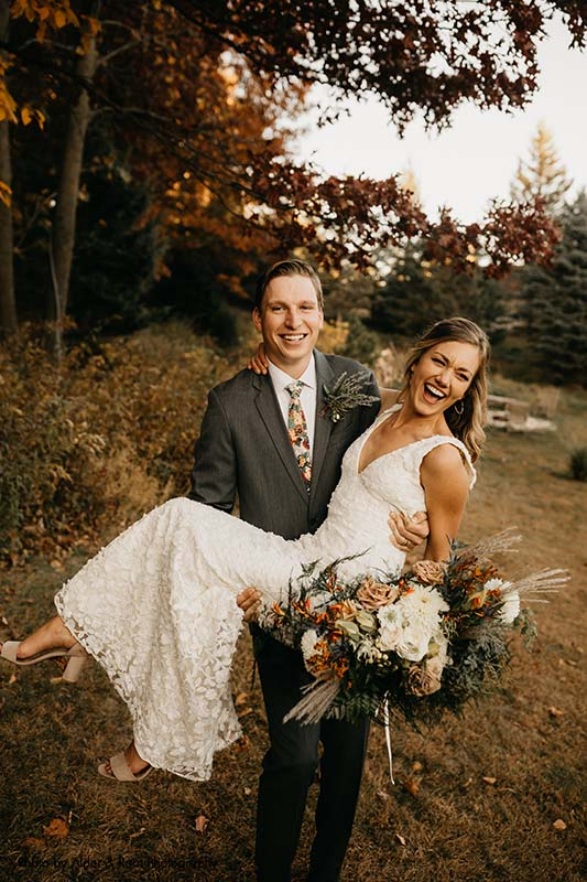 Groom lifts up bride outdoors