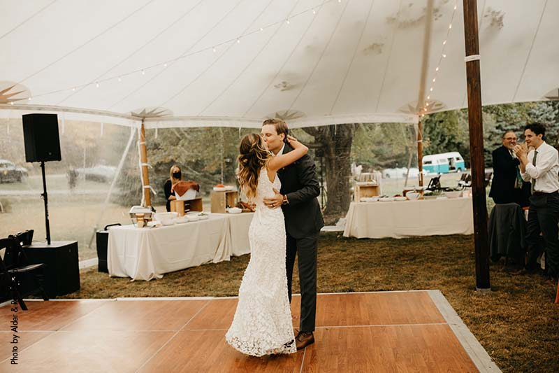 Bride and groom share first dance under outdoor wedding tent