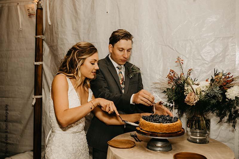 Bride and groom cut cheesecake