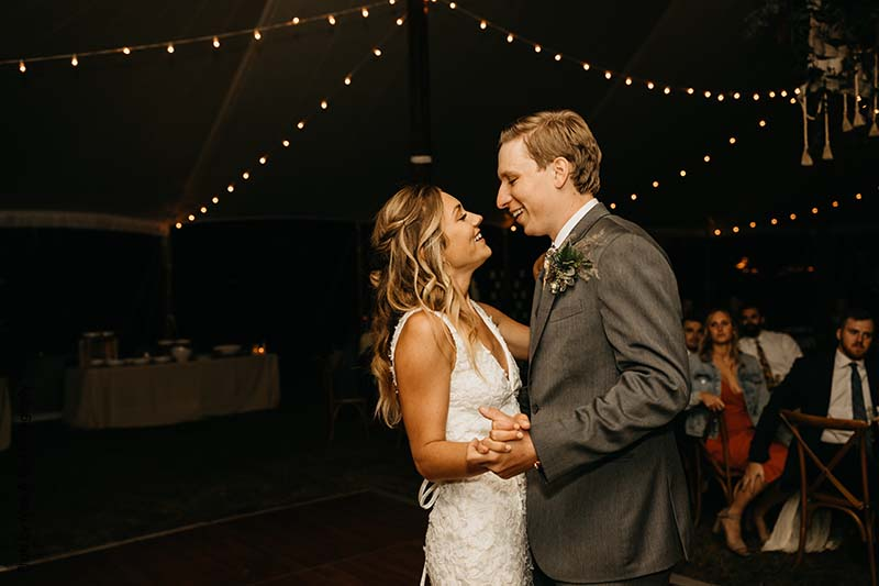 Bride and groom dance under string lights in outdoor tent