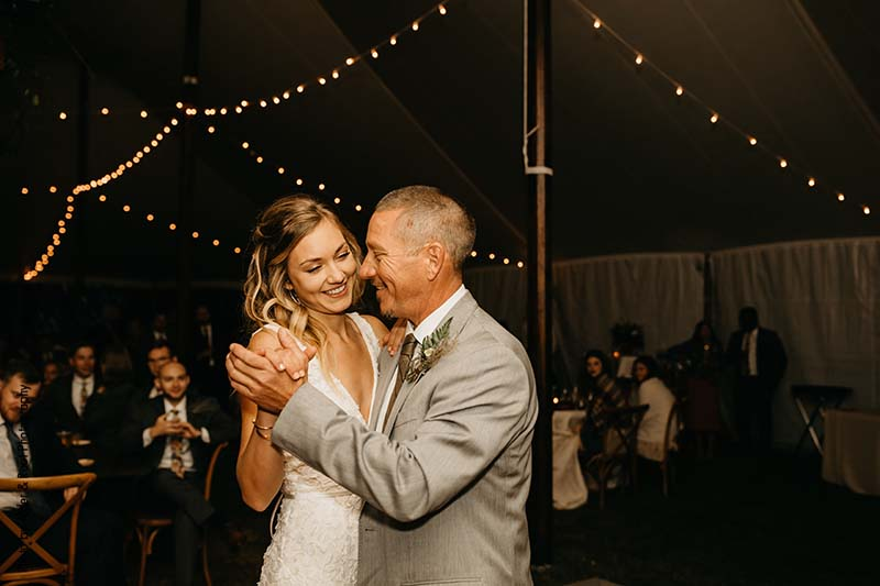 Bride and her father share dance on the dance floor in outdoor tent