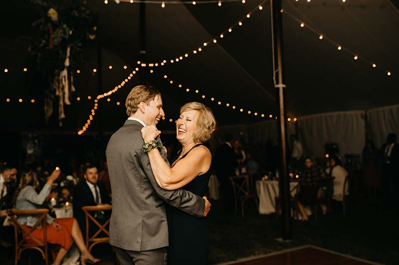 Groom and his mother share dance on the dance floor in outdoor tent