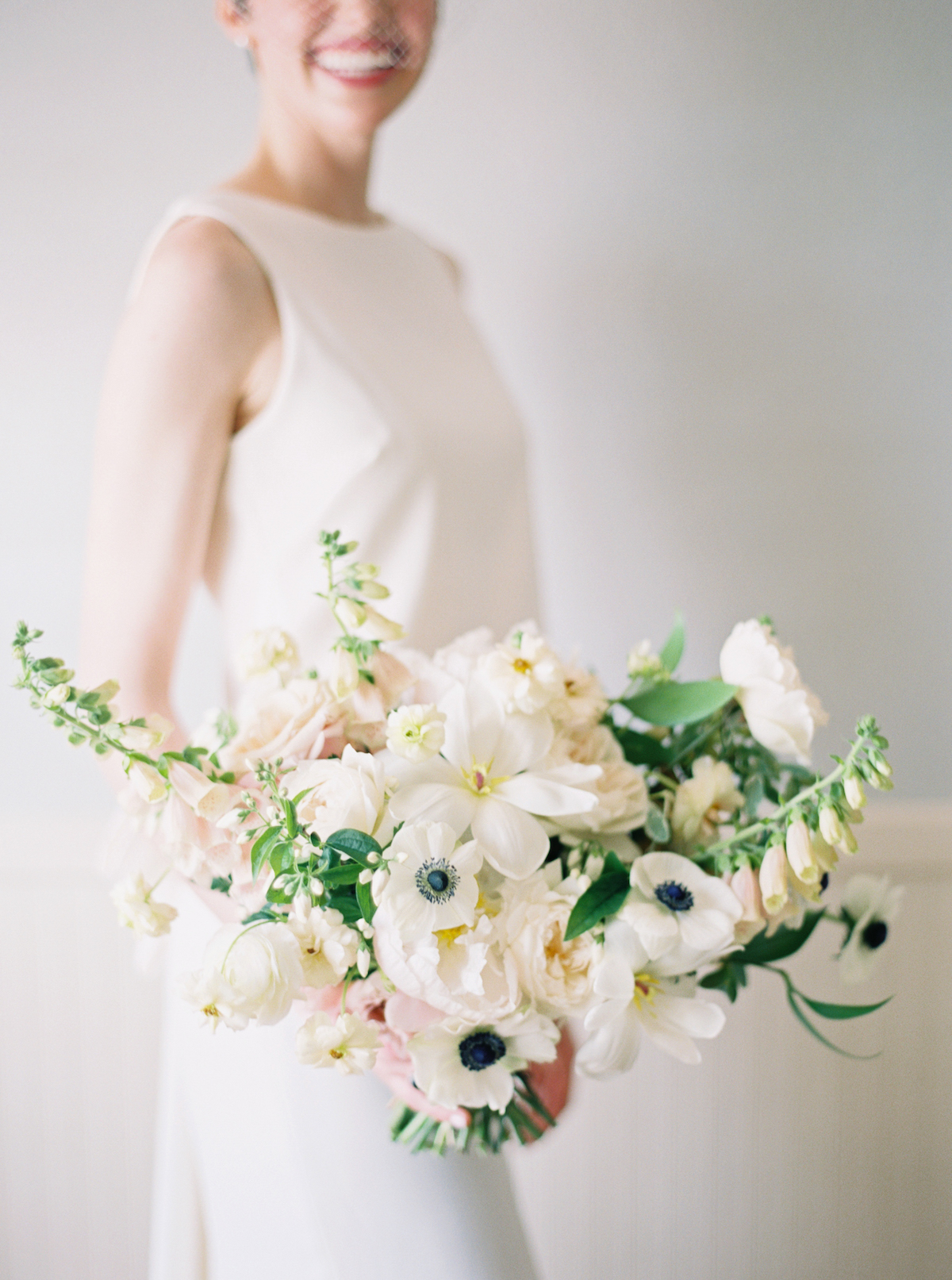 White spring bridal bouquets with tulips, anemones, peonies, roses, and ranunculus