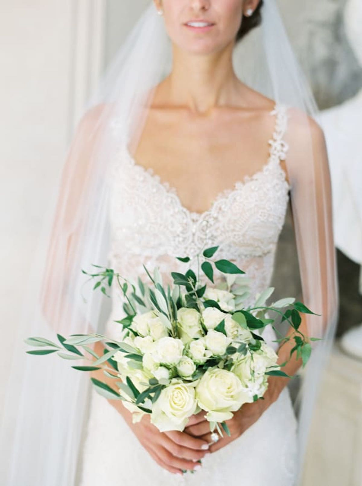 Bride poses with white rose bridal bouquet
