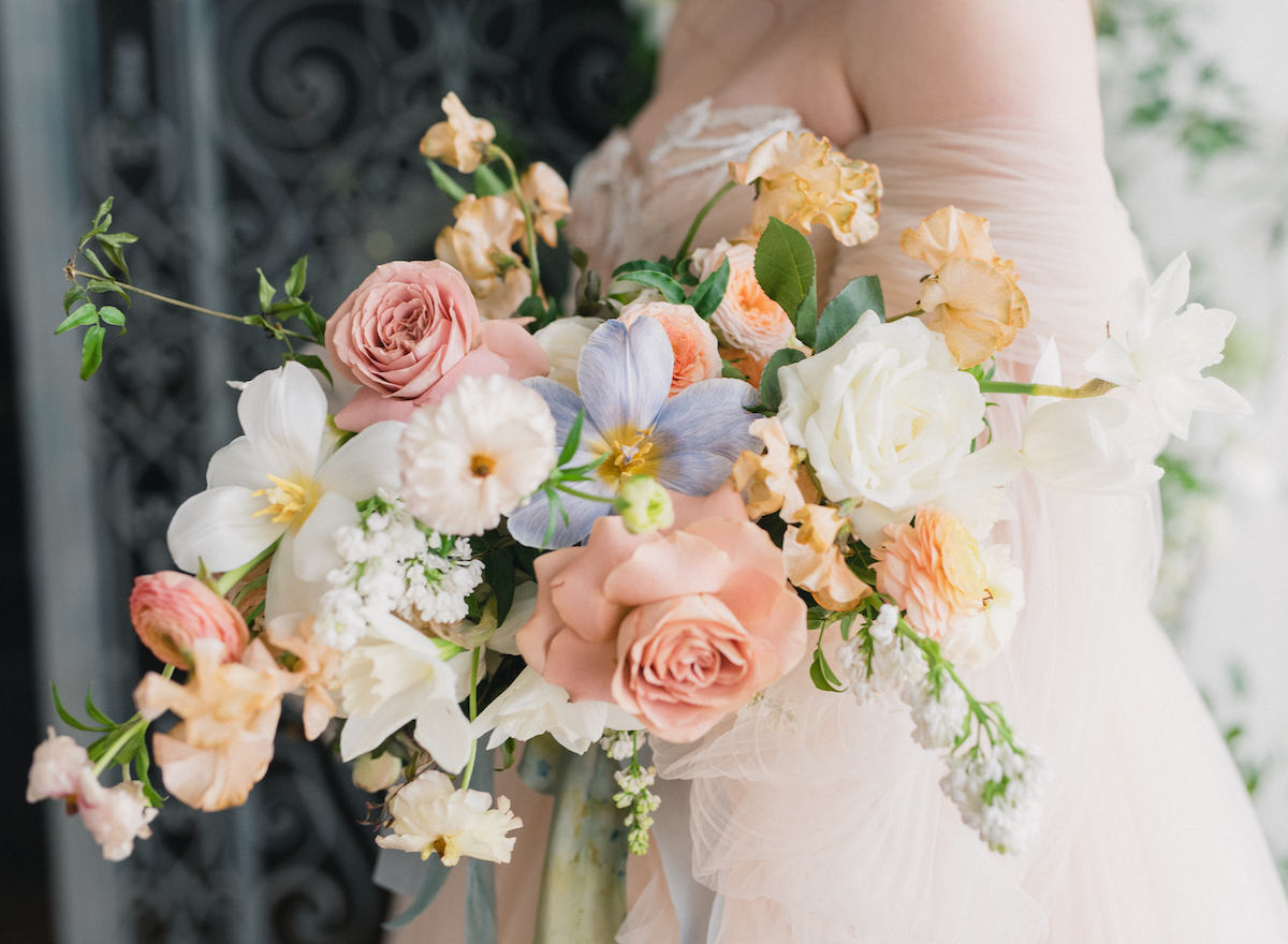 Spring bridal bouquet with peach, pink, and blue pastels